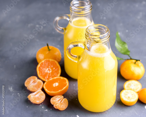 Foto op Canvas Sap Two bottles of citrus juice served with fresh whole and slice citrus on gray background