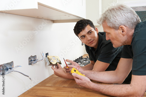 Photo Electrician With Apprentice Working In New Home