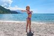Cute Caucasian girl in swimsuit doing exercises on sea coast