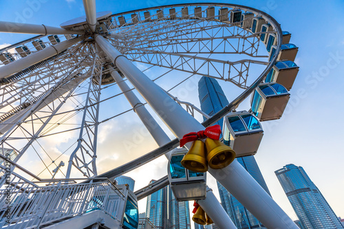 The popular icon Observation Wheel in Hong Kong island at twilight near Ferry Pier arera with landmark buildings in background Poster