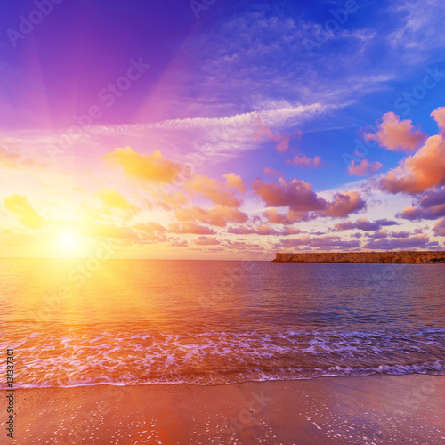 Foto op Canvas Baksteen Beautiful colorful sunrise at the sea with dramatic pink clouds over blue sky and soft waves. Beauty world natural outdoors travel background with sun shining