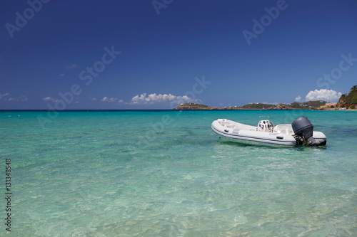 Dinghy with outboard motor anchored in a tropical bay Canvas Print