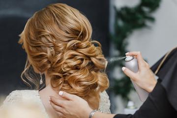 Glavni stilist čini mladenku vjenčanom frizurom koristeći lak u spreju