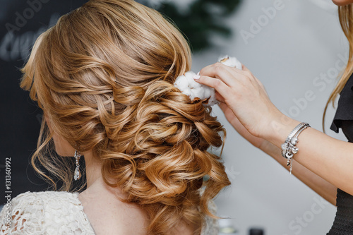 Fotografie, Obraz  Hair stylist or florist makes the bride a wedding hairstyle with