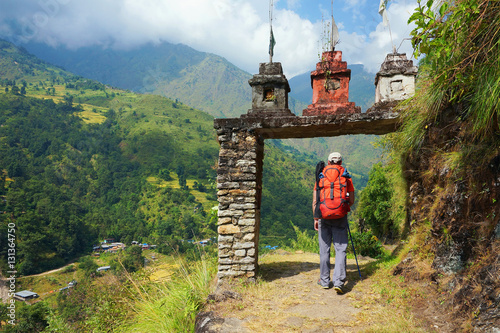 Fotobehang Nepal Tourist, a man, enter the gate to nepalese village at the valley on Annapurna Circuit Trek, in Annapurna Himal, Himalaya, Nepal, Asia