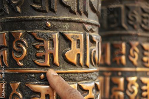 Fotografia  A human finger of local man indicates the buddhist sign Om, written in stylized Tibetan font on the old prayer wheel, in Kathmandu, Nepal