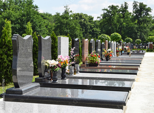 Tombstones in a row in the public cemetery Fototapeta