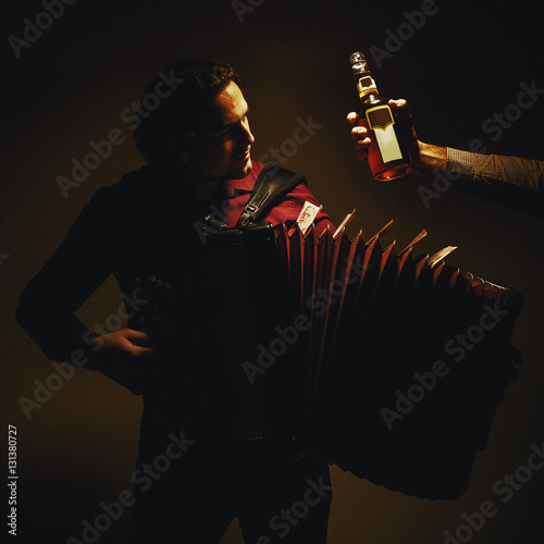Fotografia, Obraz Chromatic Accordion Player And Bottle of Spirit Drink