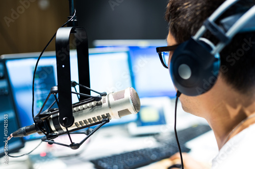 young man dj works in modern broadcast studio
