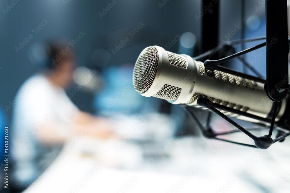 Fototapeta young man dj works in modern broadcast studio