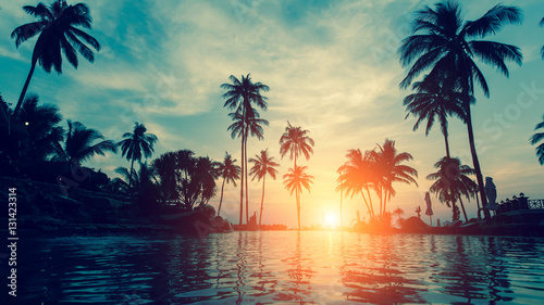 Poster de jardin Arbre Beautiful tropical beach with palm trees silhouettes at dusk.