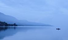 Lonely Fisherman In Foggy Mountains, Lake Toba, Indonesia.