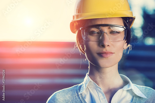 Fotografiet  beautiful woman civil engineer close up portrait in front of a sunset background