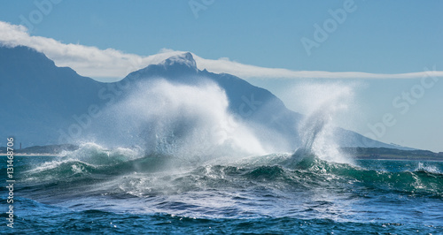 Stickers pour portes Eau Seascape. Clouds sky, waves with splashes. mountains silhouettes on the background. False bay. South Africa.