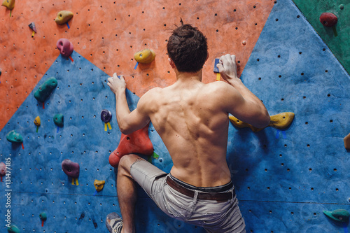Fotografía  Muscular and fit topless man exercise bouldering and climbing indoor at artifici
