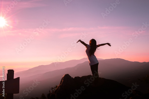 The Silhouette Of A Woman In Yoga Pose On Mountain At Sunset