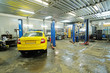 Yellow taxi under repair in a car repair station
