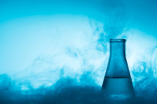 Chemical Glass Test Tube With Liquid And Steam Or Smoke Backlight On Blue Background With Copy Space