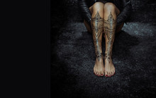 Closeup Woman Legs With Henna Tattoo Over Black Stone Floor