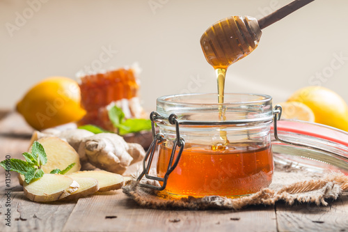 Photo  Honey in jar with ginger and lemon