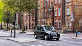 Fototapeta Londyn - Black taxi on a london street