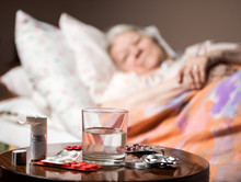 Sick Old Woman Lying In Bed At Home