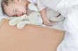 Cute baby girl sleeping on the bed with a toy bunny and blank board