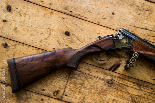 Fotografia Shotgun charged with bullets and spare bullets on wooden floor