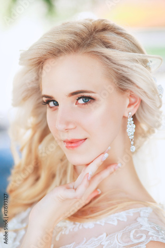 Beautiful bride. Wedding hairstyle and make up.Young bride in wedding dress holding bouquet