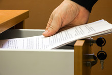 Man Puts Or Takes The Documents From The Drawer