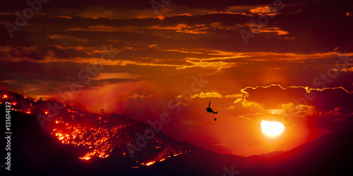 Burning Wildfire at Sunset with helicopter and water bucket fire fighter