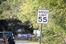 "White Sign With ""speed Limit 55"" Printed In Black On Country Roa"