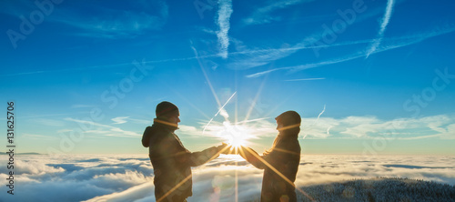 Photo  The Silhouette of man and woman with sun in hands standing on the top of mountai