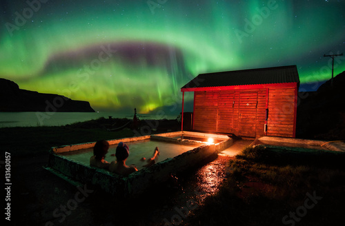 Relaxing in geothermal hot pool under northen lights (Aurora Borealis) in Iceland