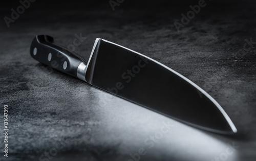 Fotografia Knife. Kitchen knife lying on an modern concrete cutting board.