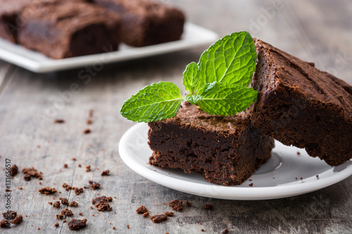 Chocolate brownie pieces on wooden background