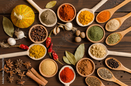Poster Spices Set of Indian spices on wooden table - Top view