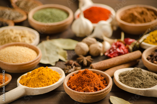 Colorful powder spices and herbs on the wooden table Canvas Print