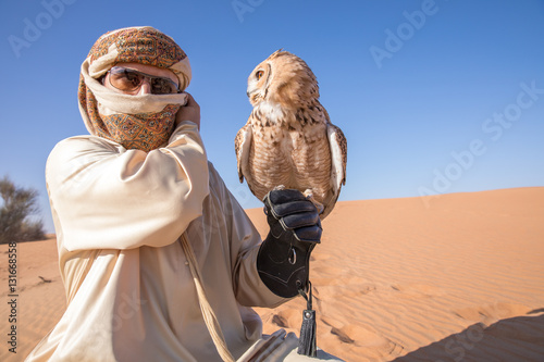 Poster Abou Dabi Young male pharaoh eagle owl (bubo ascalaphus) with a traditionally dressed arab male during a desert falconry show in Dubai, UAE.