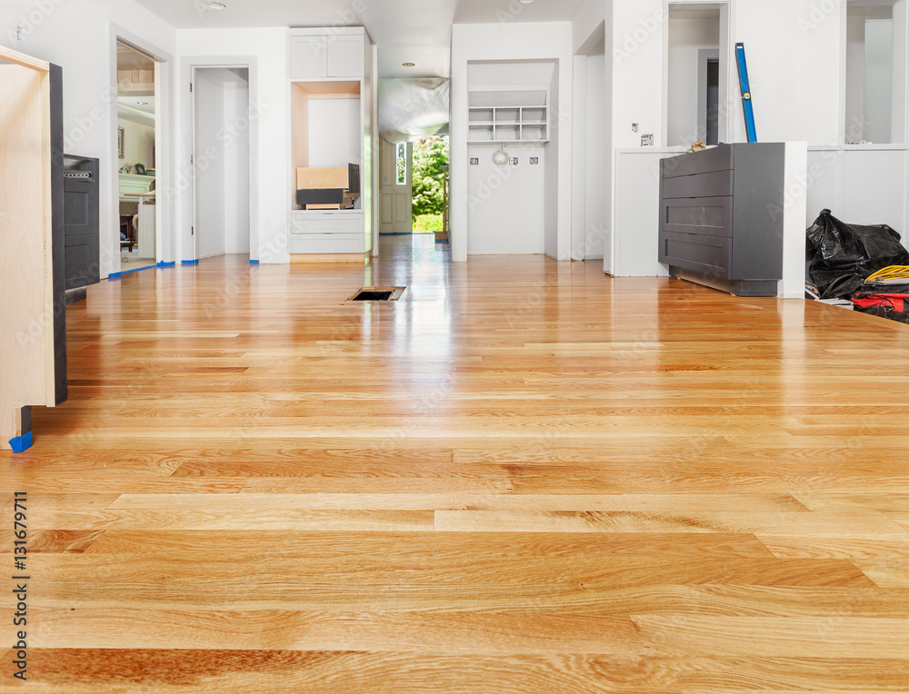Fototapeta Remodeled kitchen has existing hardwood floor patched and refinished