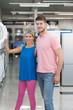 Beautiful Young Couple Shopping Washing Machine In Supermarket