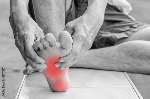 Photo  Pain in the foot. Massage of male feet. Pedicures.