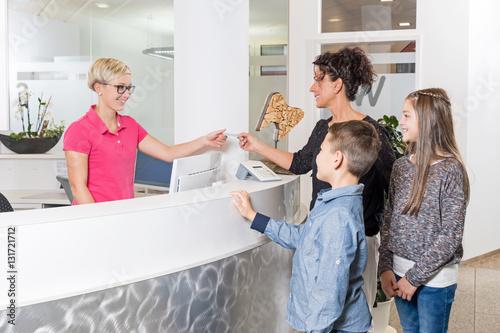 Fotografía  Mutter mit Kindern im Empfangsbereich einer Zahnarztpraxis