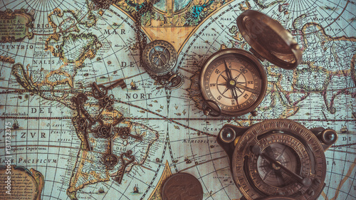 Photo Antique pirate rare items collections including with a compass, retro vintage skeleton key bottle opener, brass pocket compass with cover lid, bronze coin on ancient world map