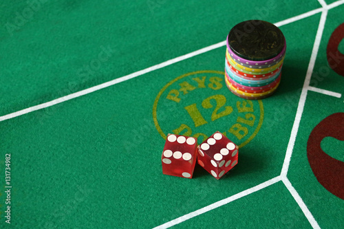 Photo  Dice craps boxcars pays double green felt with red dice many colored casino chip