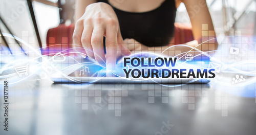 Photo  Woman using tablet pc and selecting follow your dreams.