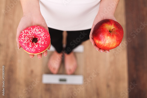 Fototapeta Diet. Woman Measuring Body Weight On Weighing Scale Holding Donut and apple. Sweets Are Unhealthy Junk Food. Dieting, Healthy Eating, Lifestyle. Weight Loss. Obesity. Top View obraz