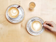 Two Coffees On A Wooden Table Seen From Above. A Woman's Hand Holds One Of The Cups While Waiting For Her Partner.