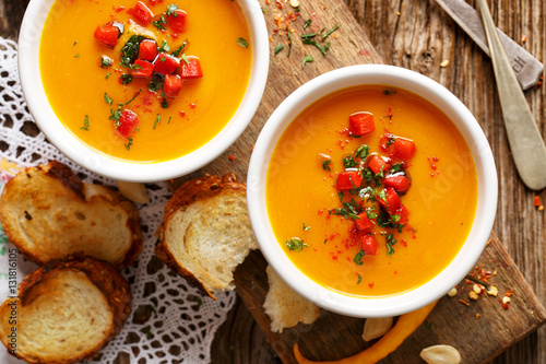 Fotografie, Obraz  Homemade pumpkin soup in a white ceramic bowl on a wooden rustic table, nutritio