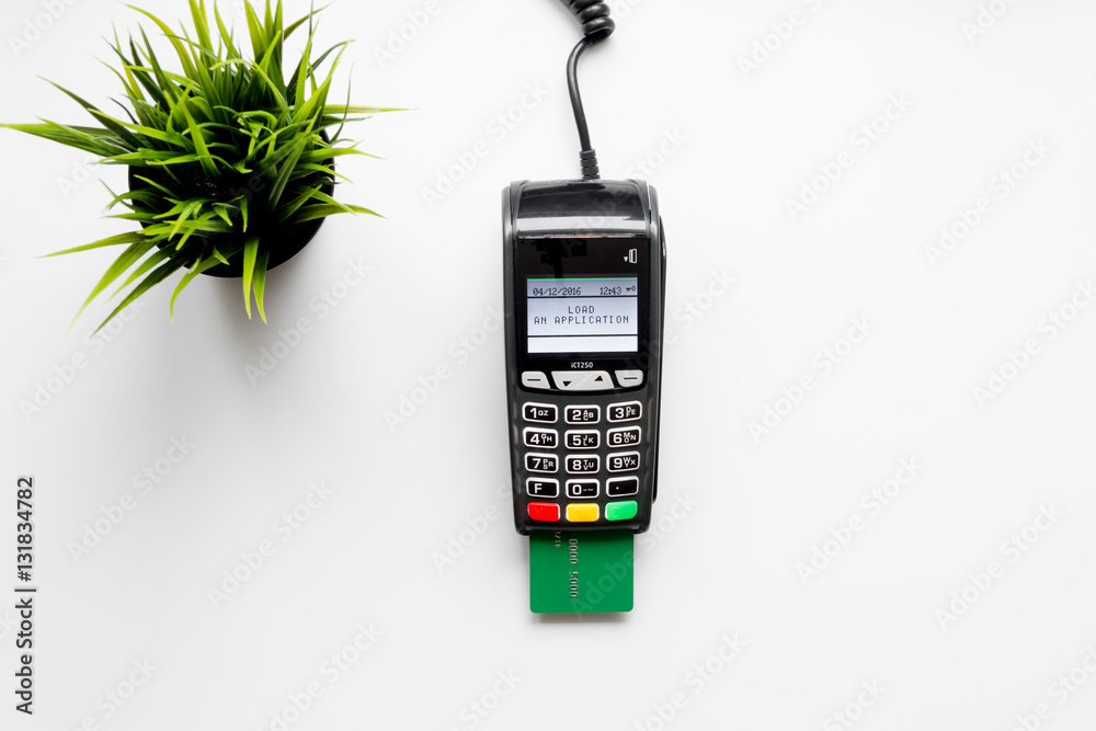Fototapeta payment terminal with card on white background top view